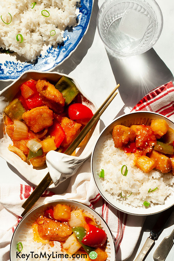 Three bowls of breaded chicken tossed in sweet and sour sauce.