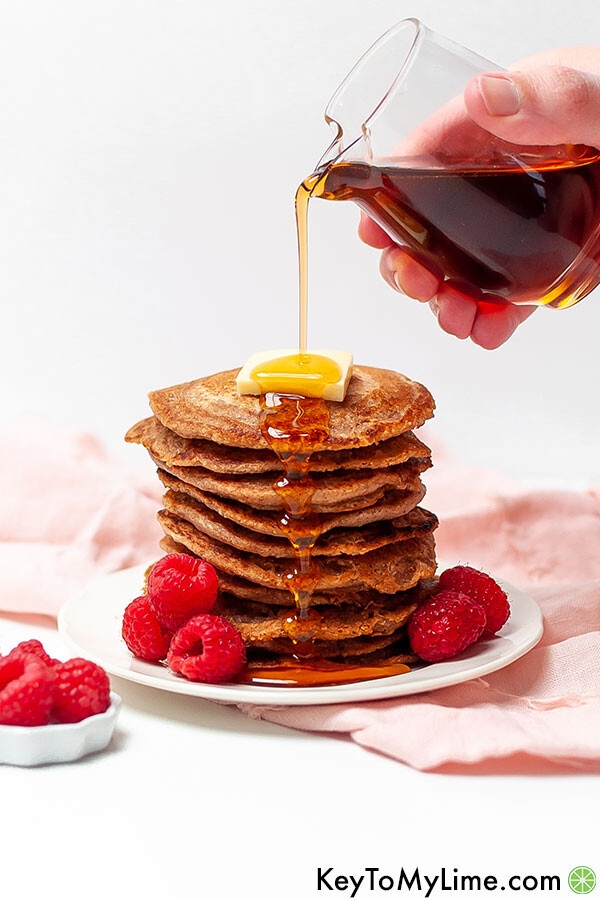 A hand pouring syrup over a stack of oat flour pancakes.
