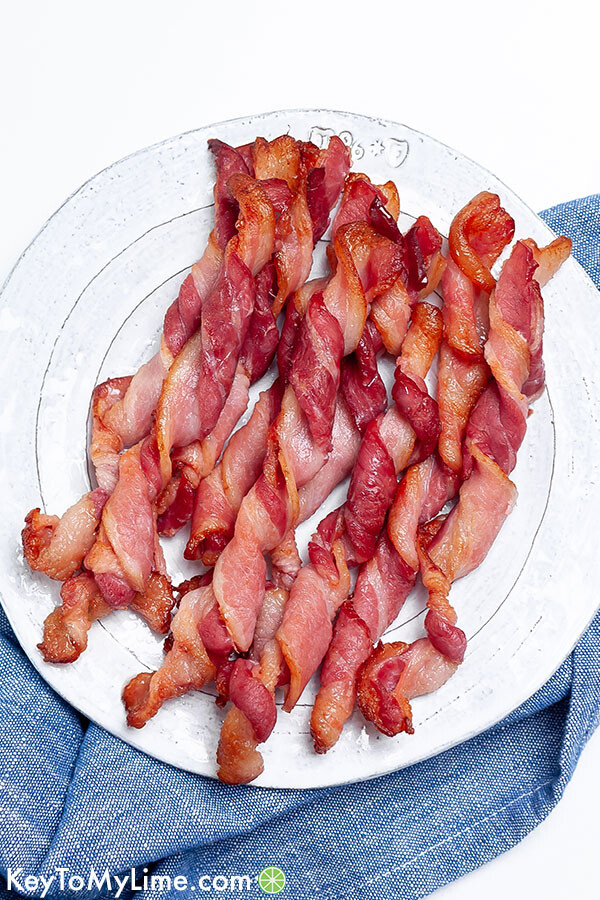 Twisted bacon on a white plate against a blue napkin.