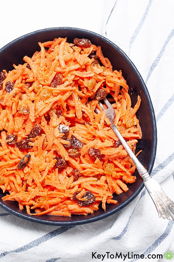 A fork in a bowl of carrot salad.