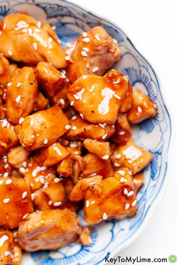 A close up image of teriyaki chicken bites in a decorated blue bowl.