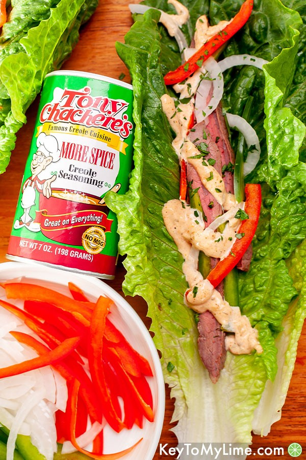An overhead image of lettuce wraps on a wood board with Tony Chachere's More Spice Seasoning.