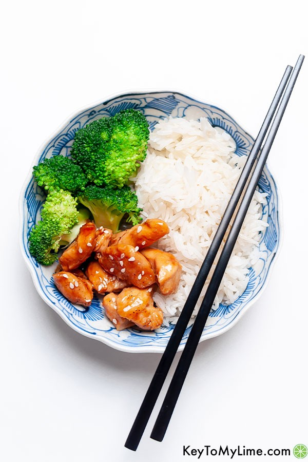 Teriyaki chicken bites with rice and broccoli in a blue and white bowl.