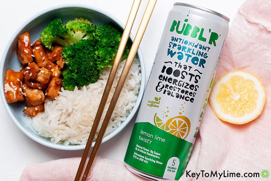 Teriyaki chicken bites with chopsticks next to a can of sparkling water.