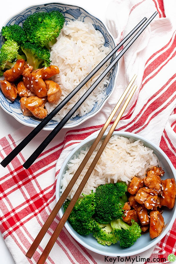 Two small bowls of teriyaki chicken bites on a red and white napkin.