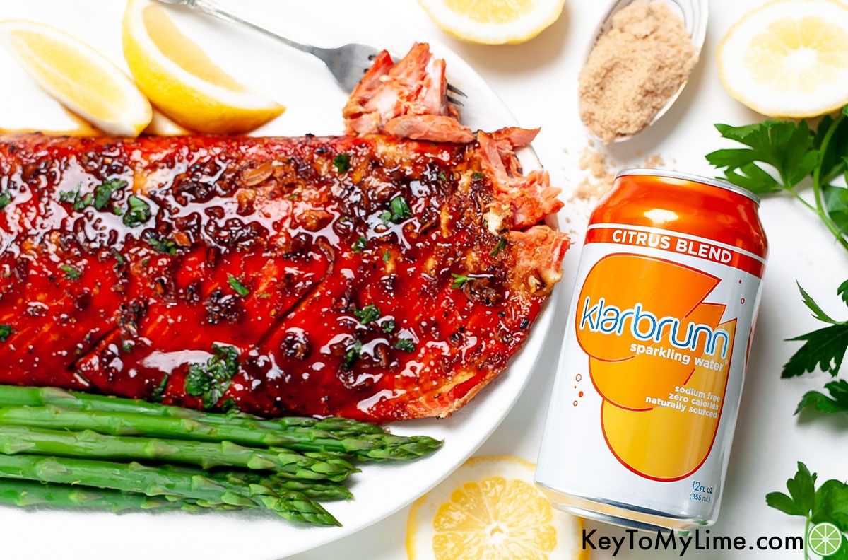 Glazed salmon next to a can of Klarbrunn sparkling water.