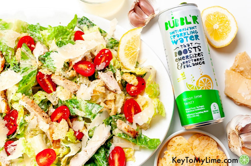 Salad on a white platter next to a can of BUBBL'R sparkling water.