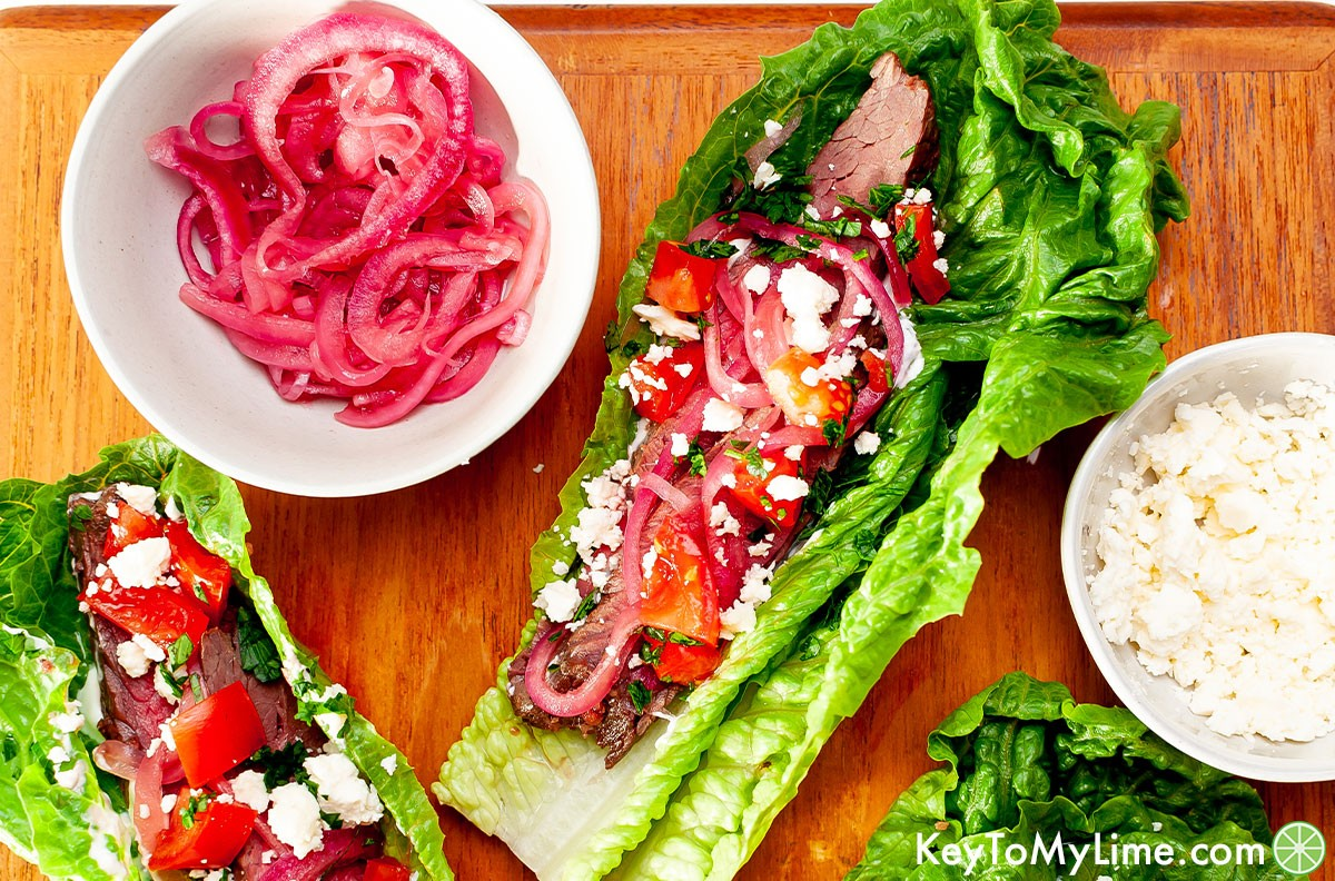 Two beef lettuce tacos next to a bowl of quick pickled red onions.