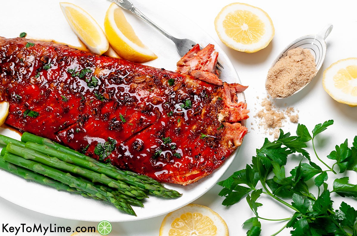 Glazed salmon surrounded by lemon slices and parsley.