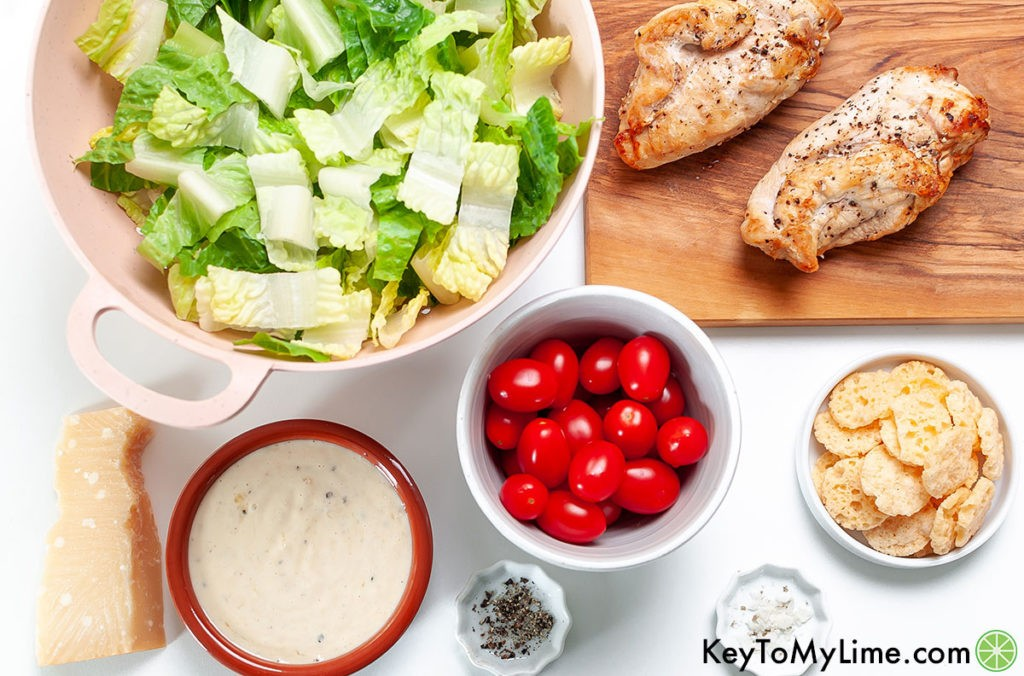 Bowls of romaine lettuce, cherry tomatoes, Caesar dressing, salt, pepper, parmesan crisps, chicken breasts, and parmesan.