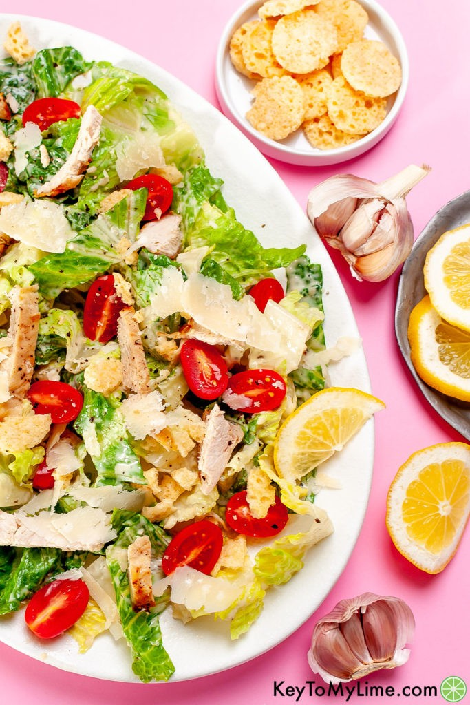 Keto Caesar salad on a pink background surrounded by lemon wedges.