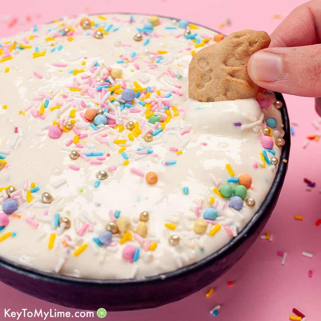 A hand dipping an animal cracker into a bowl of the best funfetti dip.