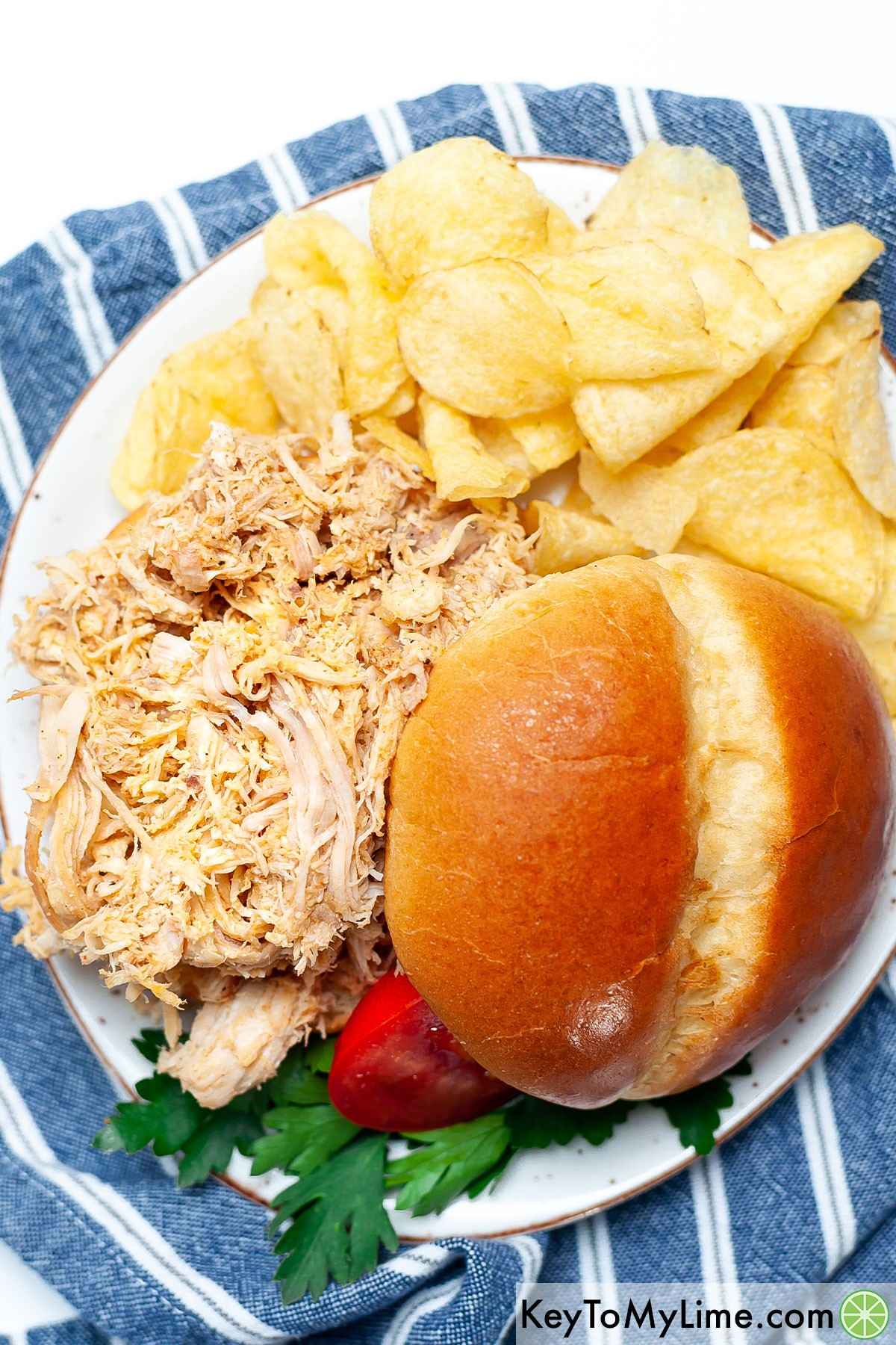 An overhead image of a pulled chicken sandwich on a plate with potato chips.