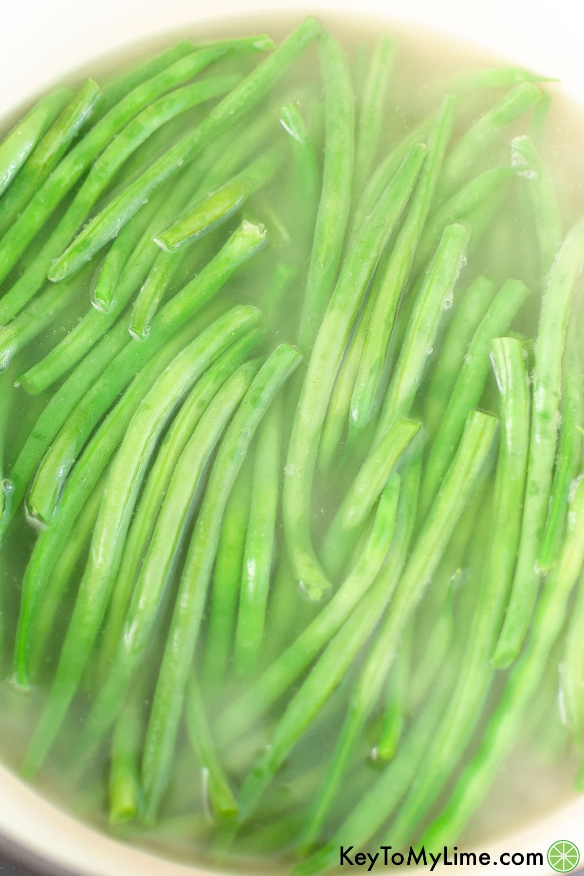 A process photo of green beans boiling in a pot.