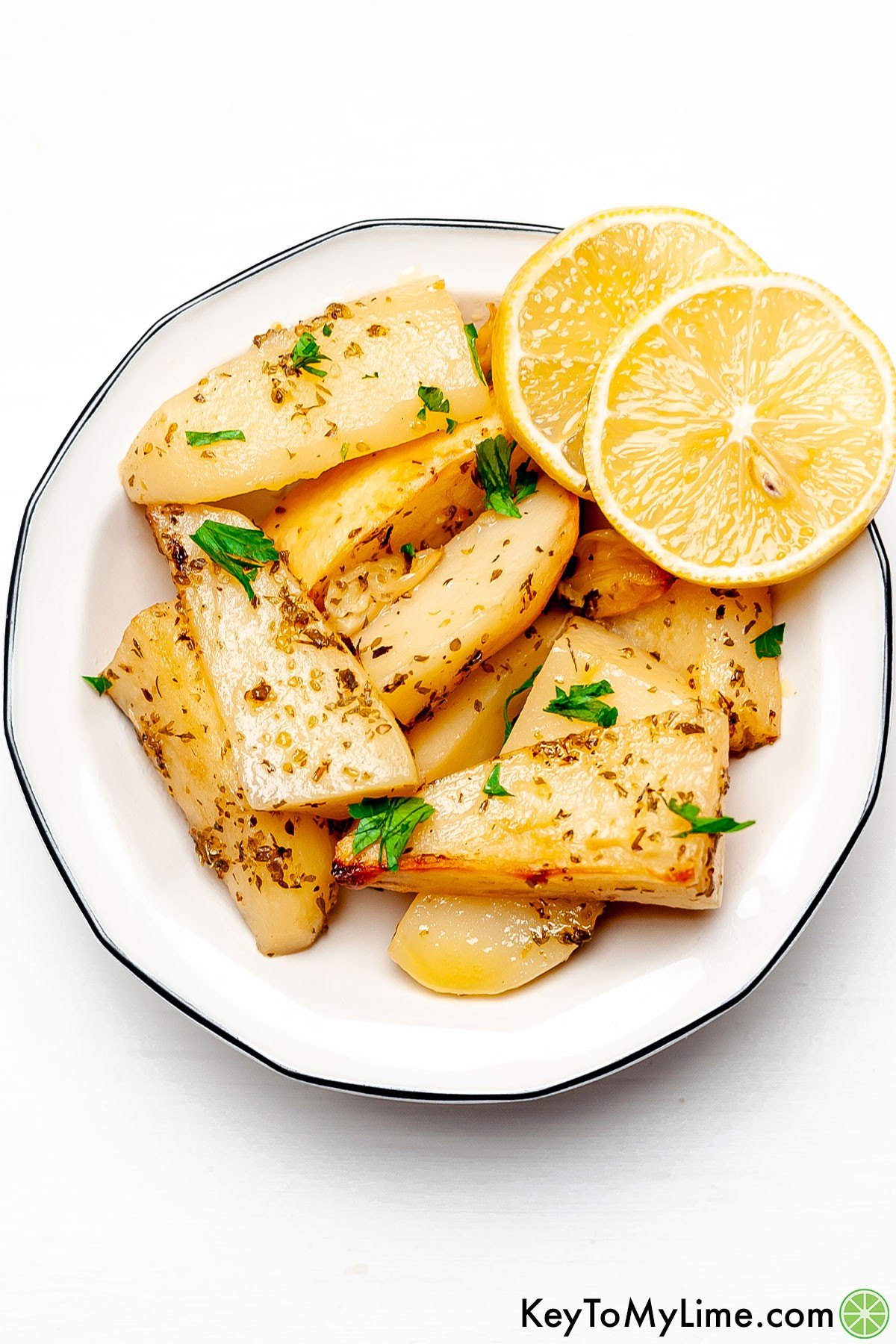 Greek potatoes in a white bowl with a black rim garnished with parsley and lemon slices.