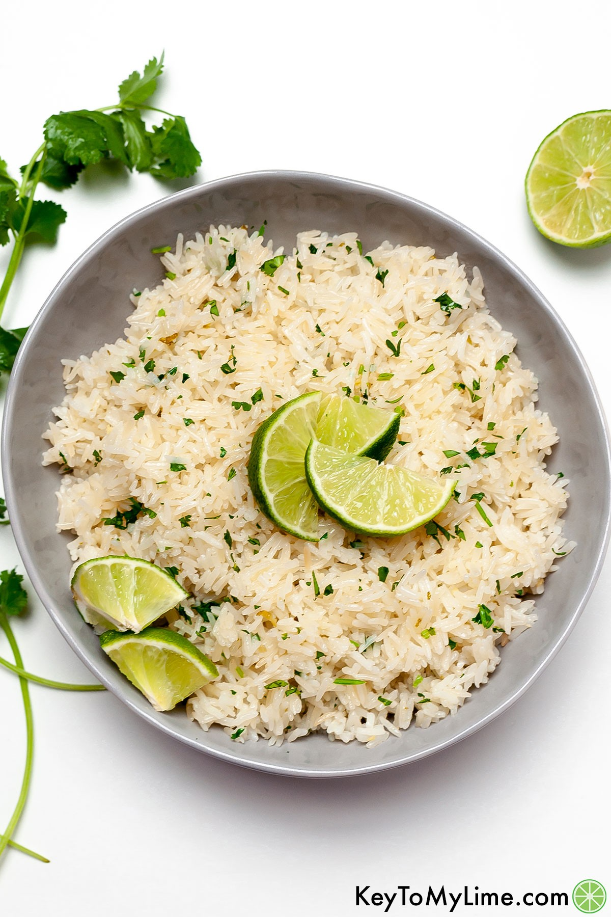 A bowl of copycat Chipotle cilantro lime rice in a bowl surrounded by lime wedges and herbs.