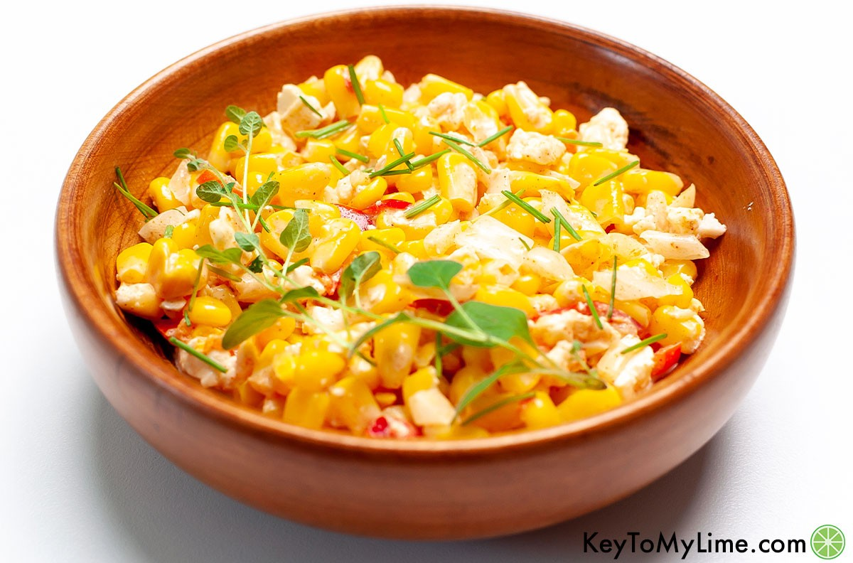 A side image of a wooden bowl filled with Mexican corn salad.