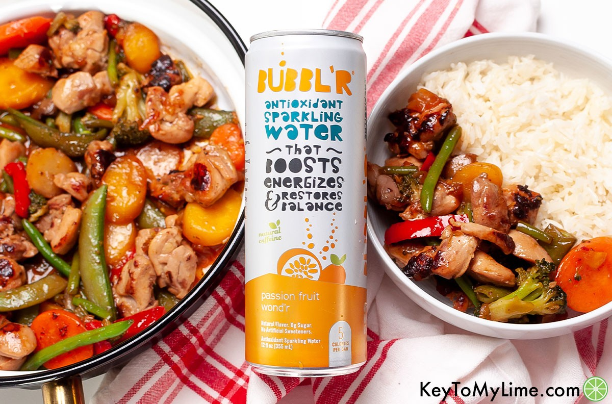 Chicken stir fry next to a can of sparkling water.