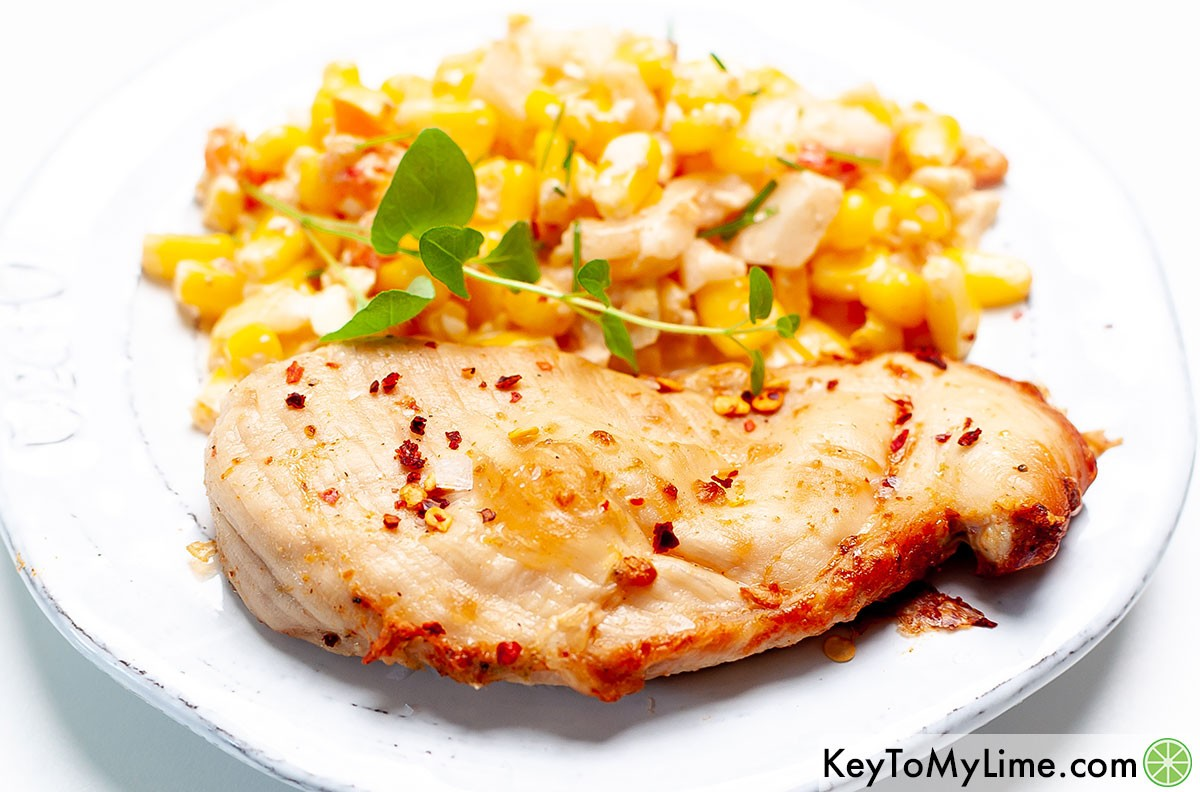 Chili lime chicken on a plate with Mexican street corn salad.