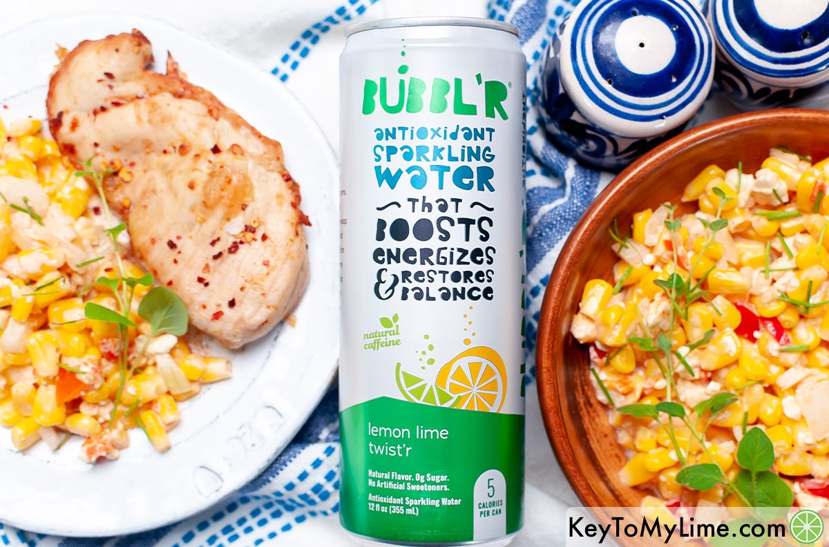 Chili lime chicken on a plate next to a can of sparkling water.