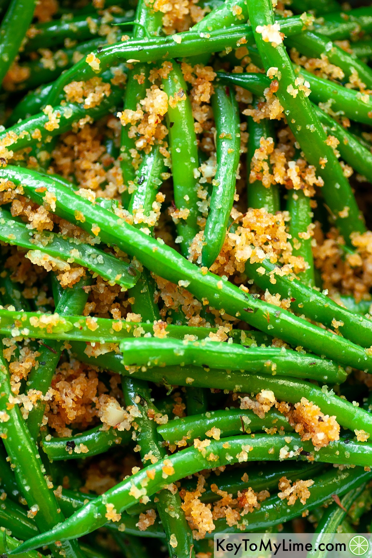 A close up image of Italian green beans coated in seasoned bread crumbs.
