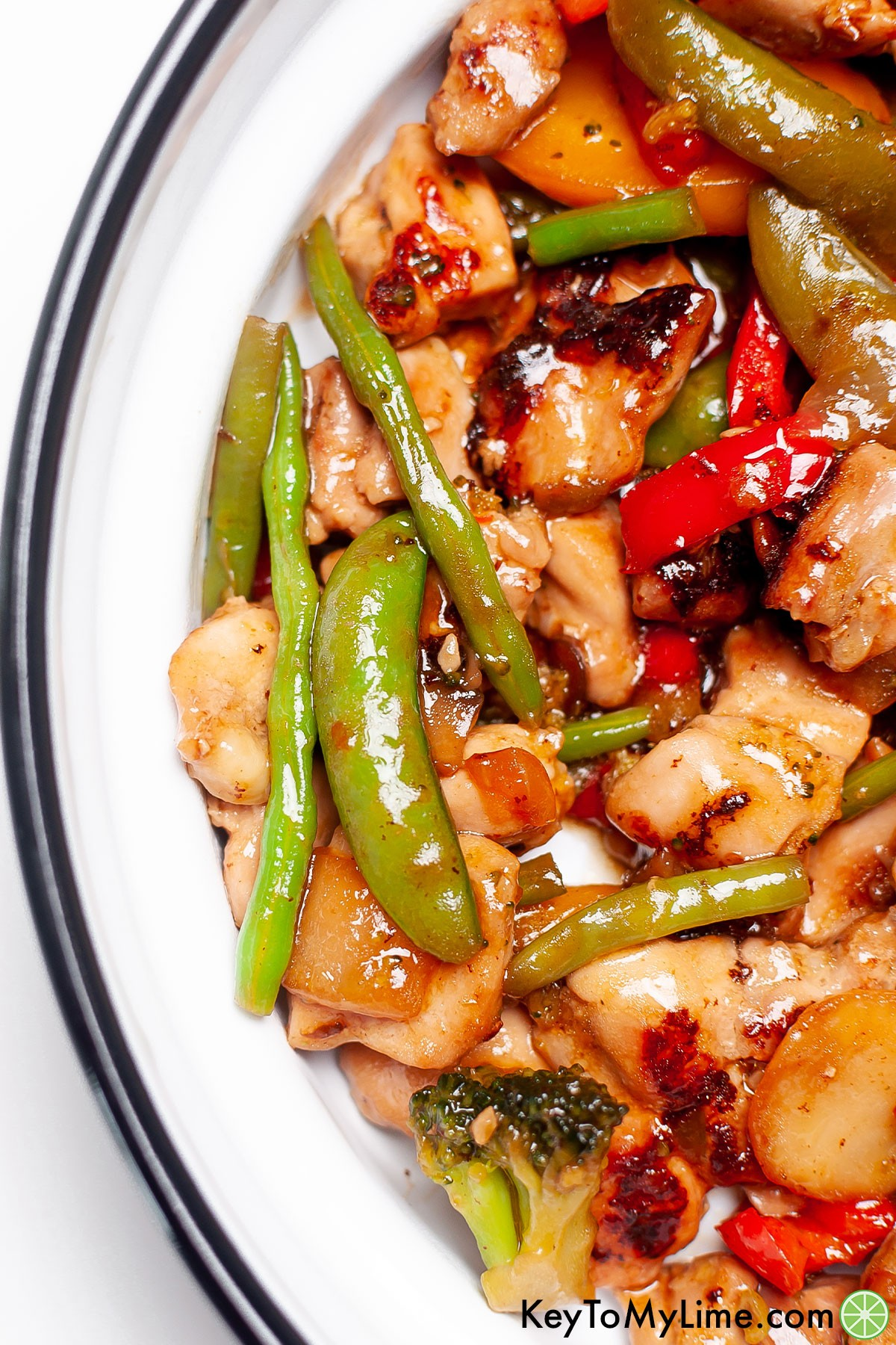 A close up of chicken stir fry in a skillet.