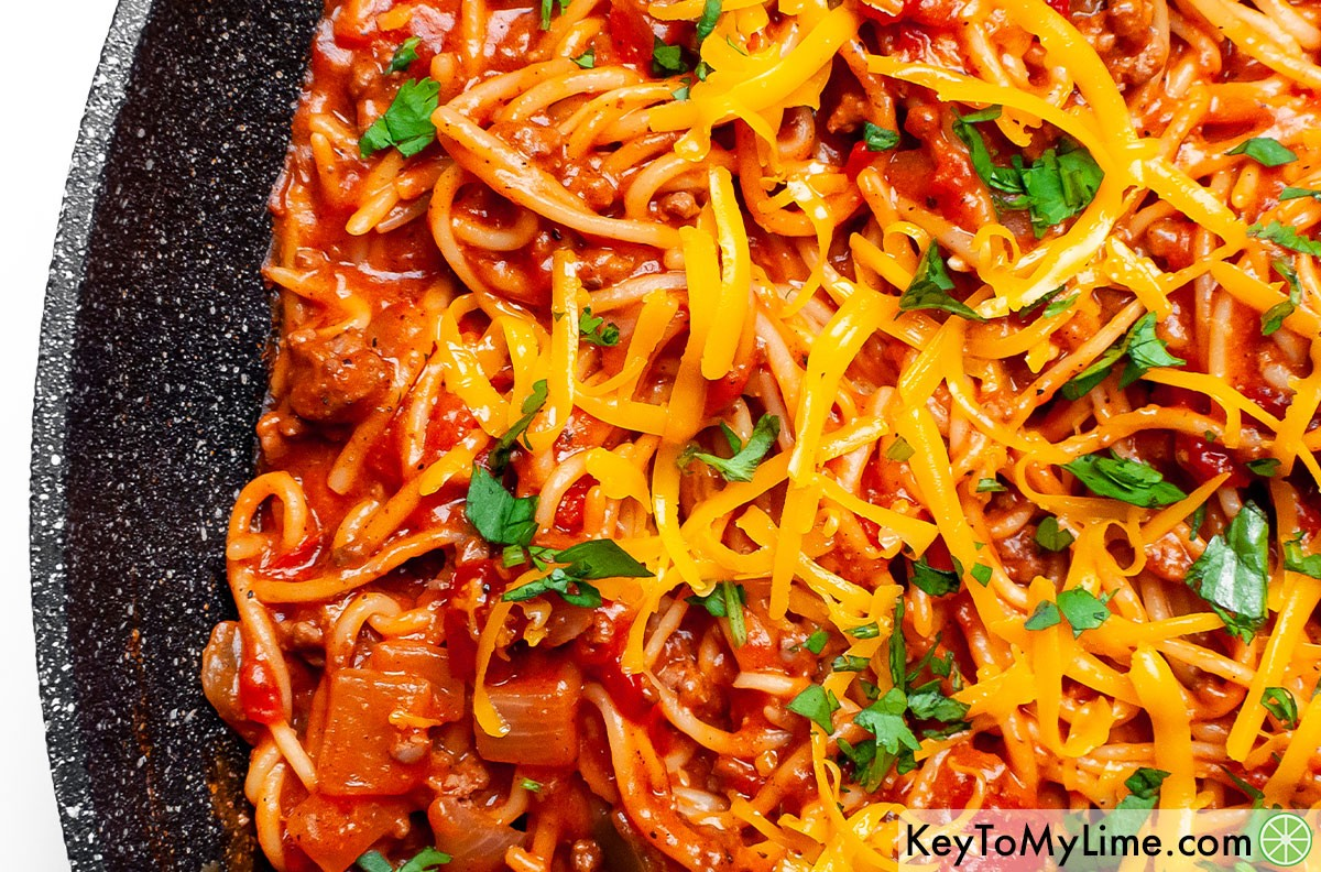 A close up image of Mexican spaghetti topped with cheddar cheese.