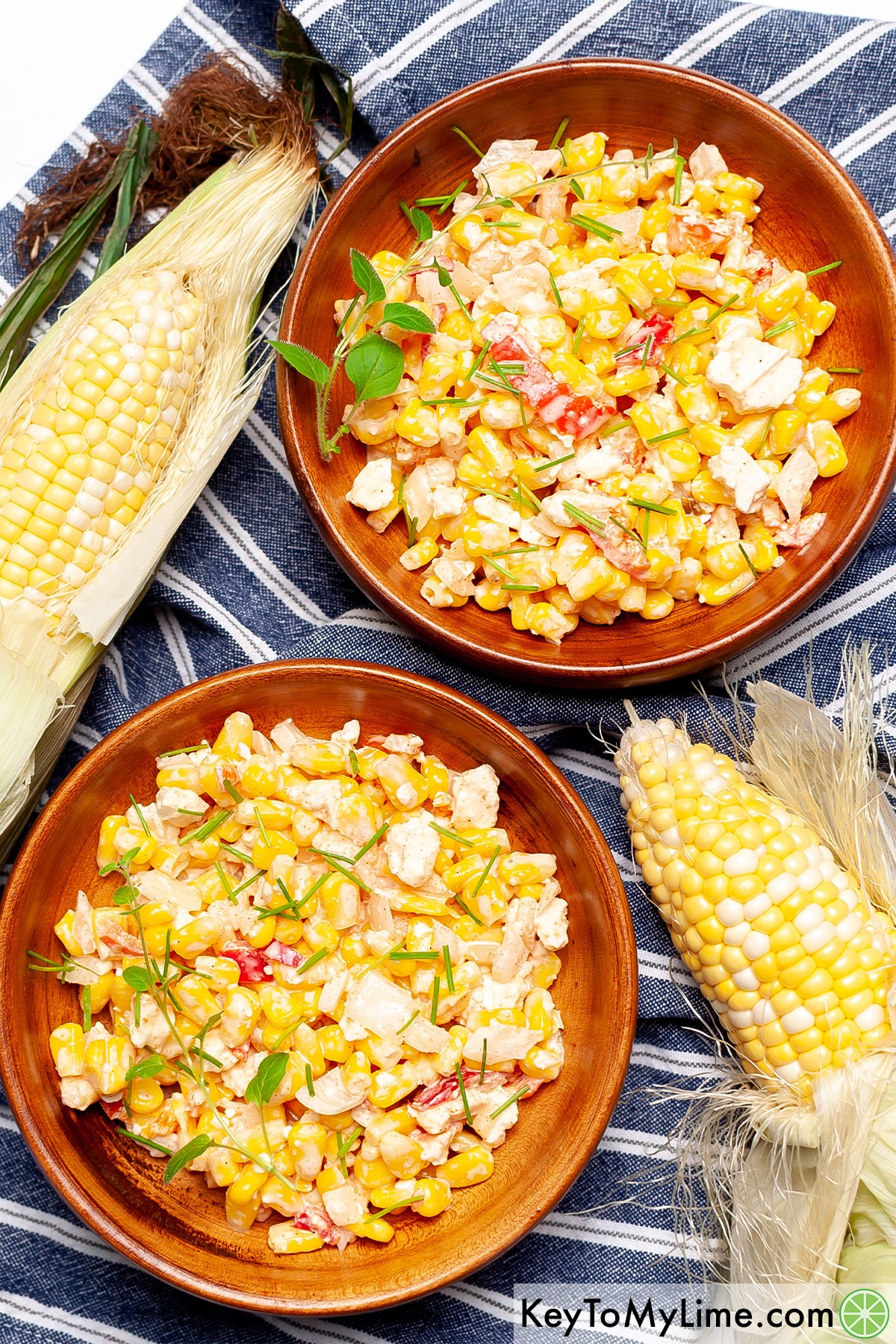 Two bowls of Mexican street corn salad next to ears of corn.