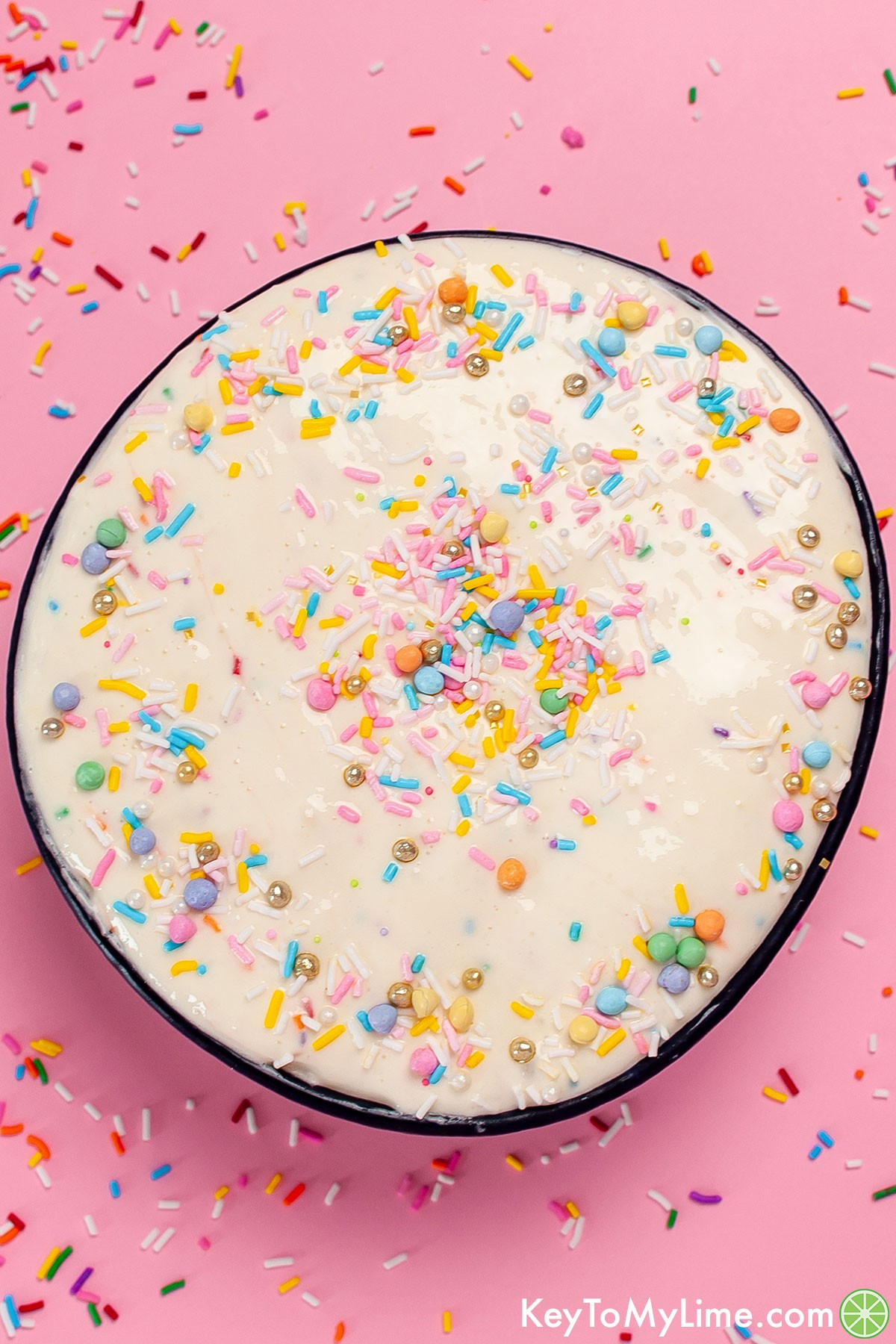 A bowl of funfetti dip against a pink background with sprinkles spread around.
