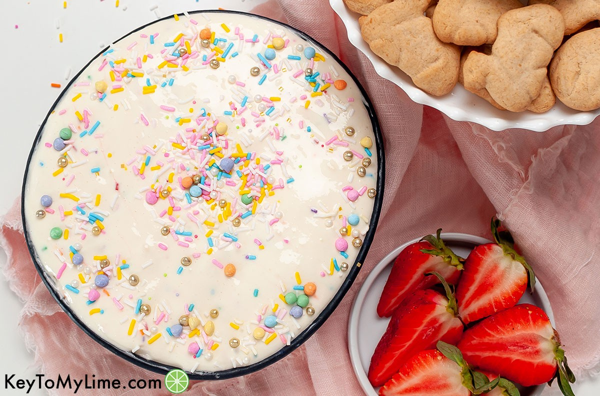 A bowl of funfetti dip next to a bowl of sliced strawberries and a bowl of animal crackers.