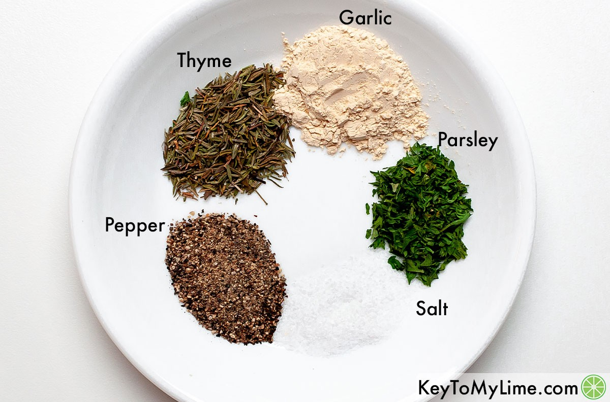 Garlic, parsley, salt, pepper, and thyme labeled on a plate.