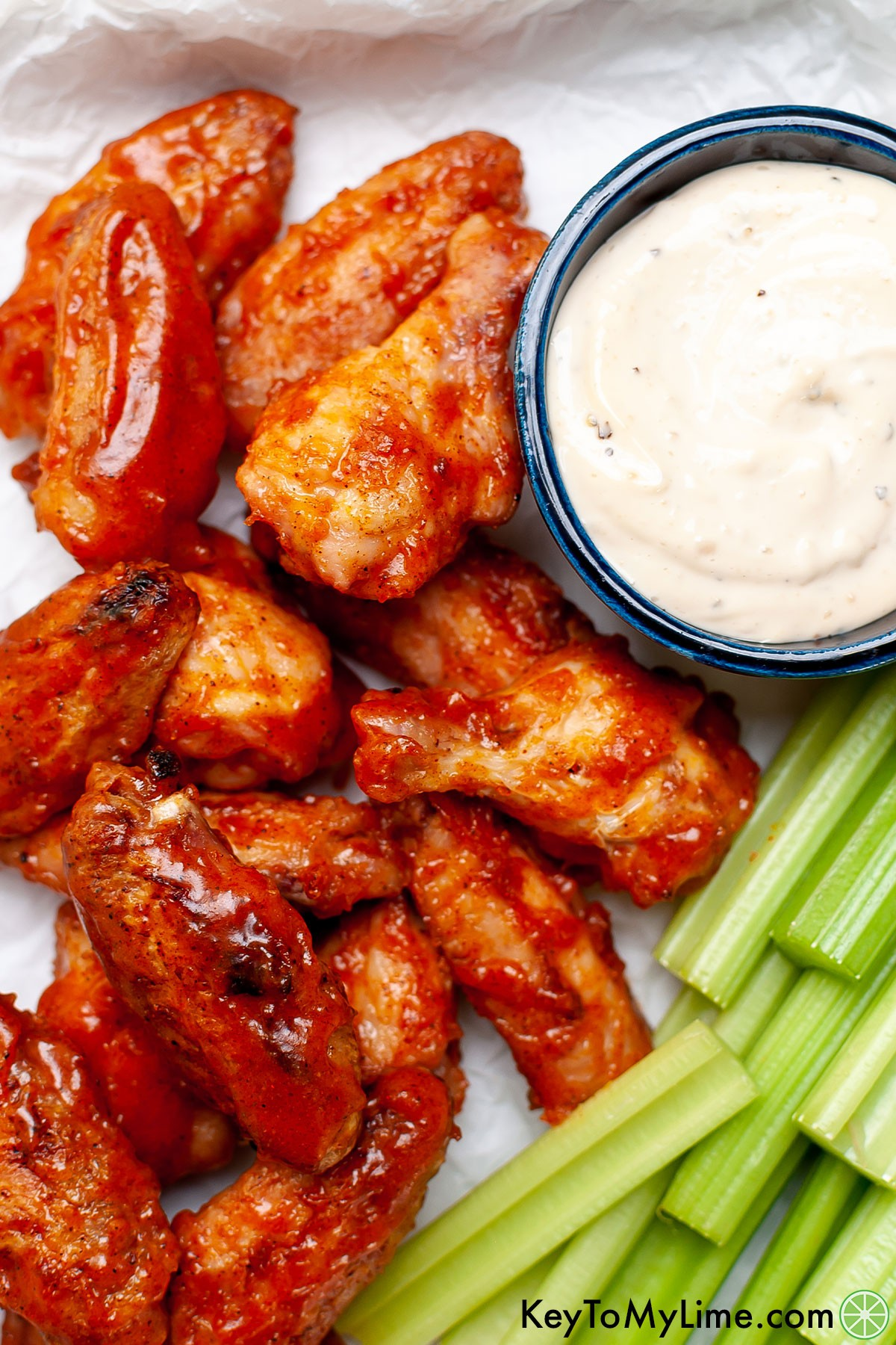 Grilled sticky wings next to celery.