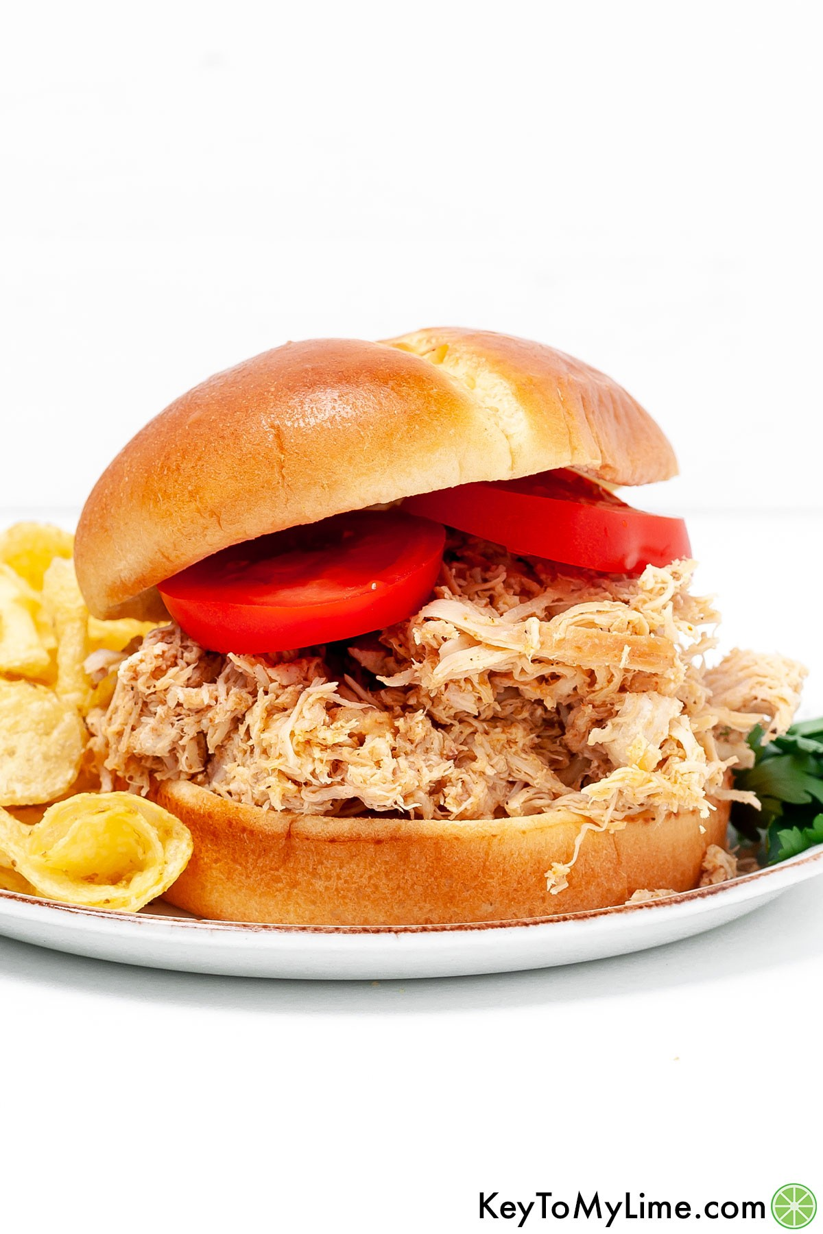A pulled chicken sandwich next to potato chips.