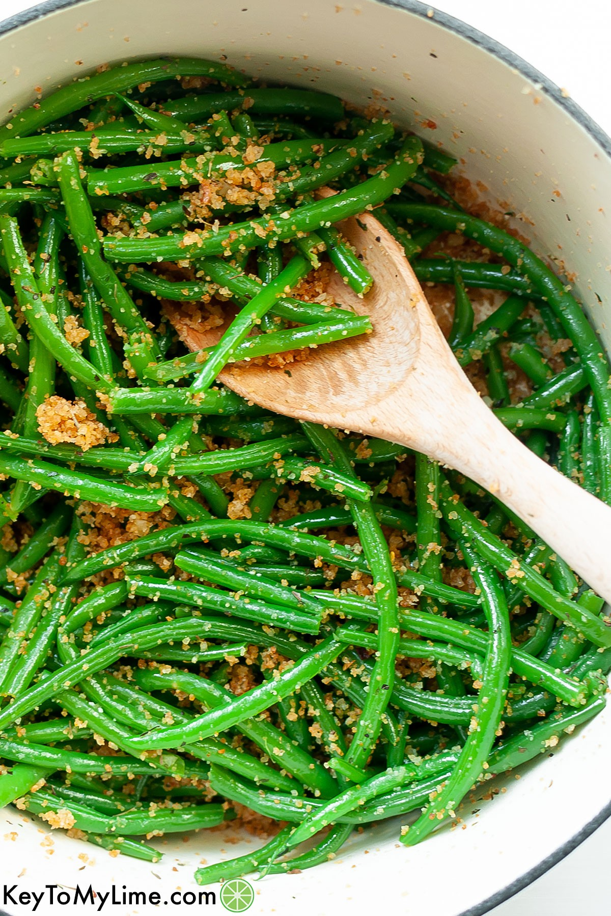 A Dutch oven filled with Italian green beans and breadcrumbs with a wooden spoon.