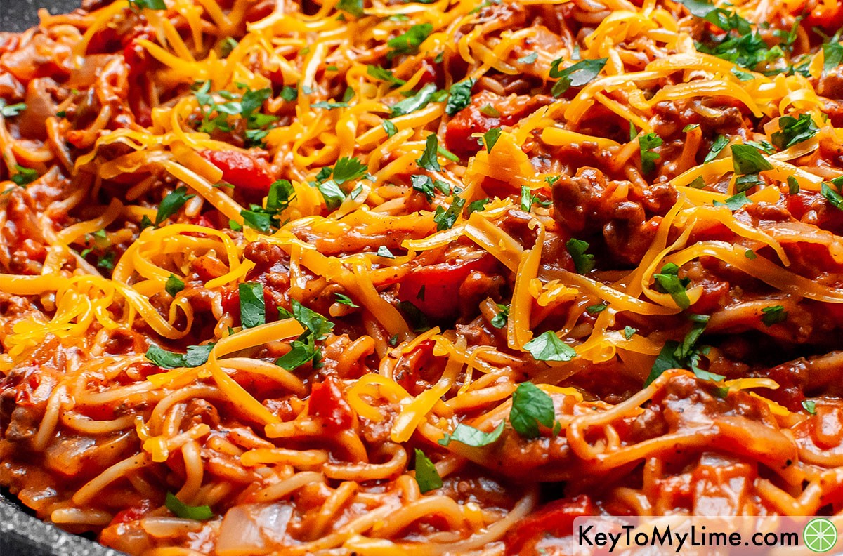 Taco spaghetti in a skillet garnished with cheddar cheese and cilantro.