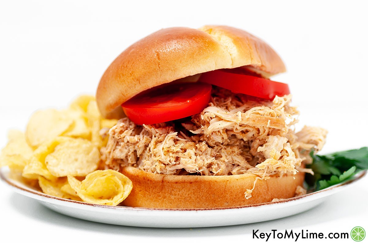 A pulled chicken sandwich next to potato chips against a white background.