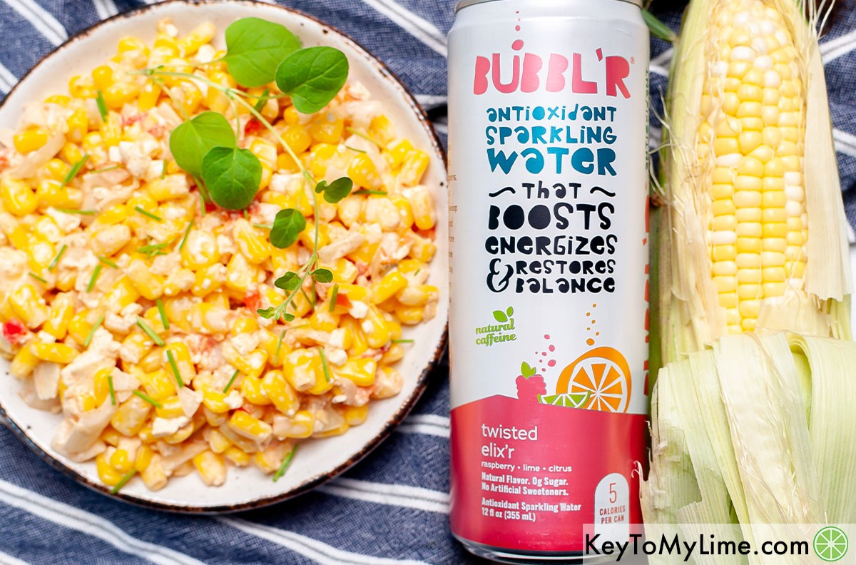A bowl of corn salad next to a can of BUBBL'R.
