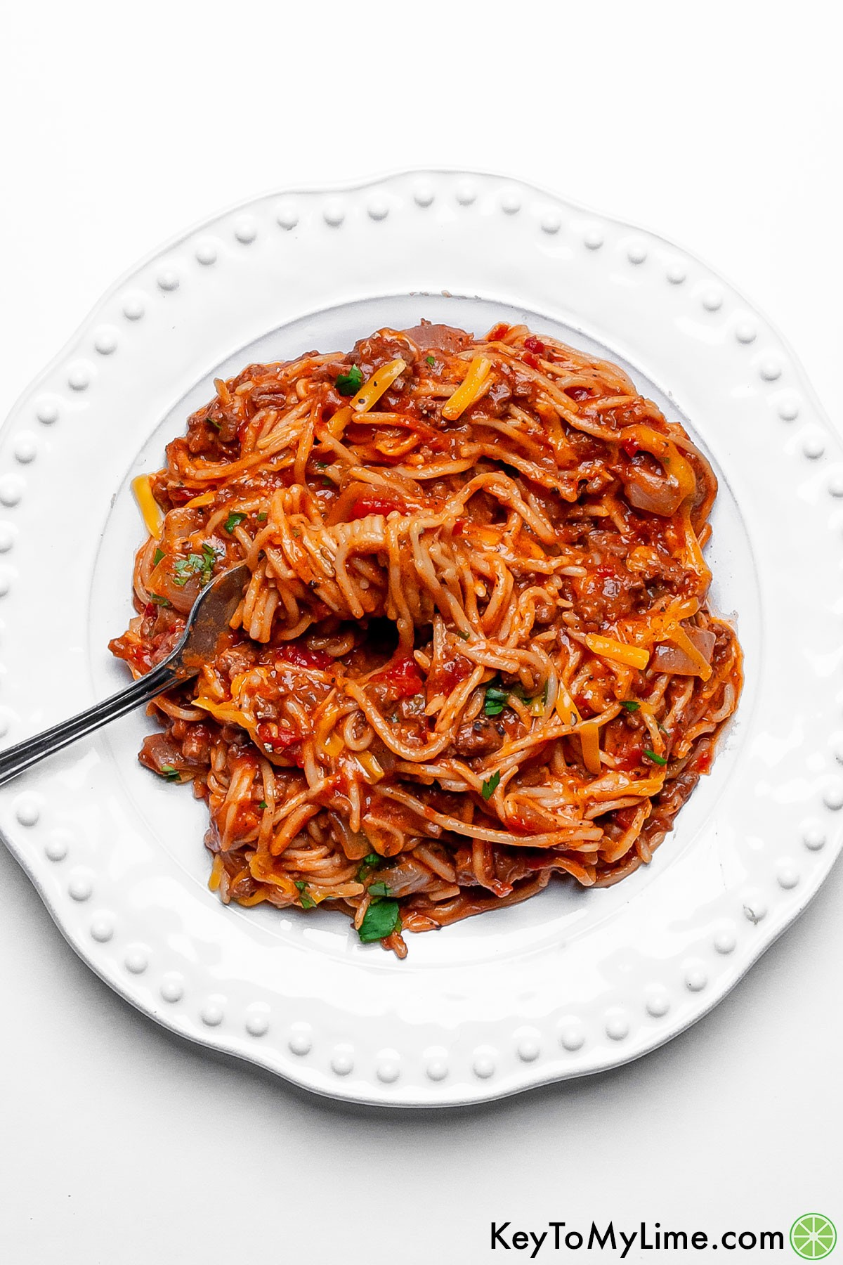 A serving of Mexican spaghetti on a plate with a fork.