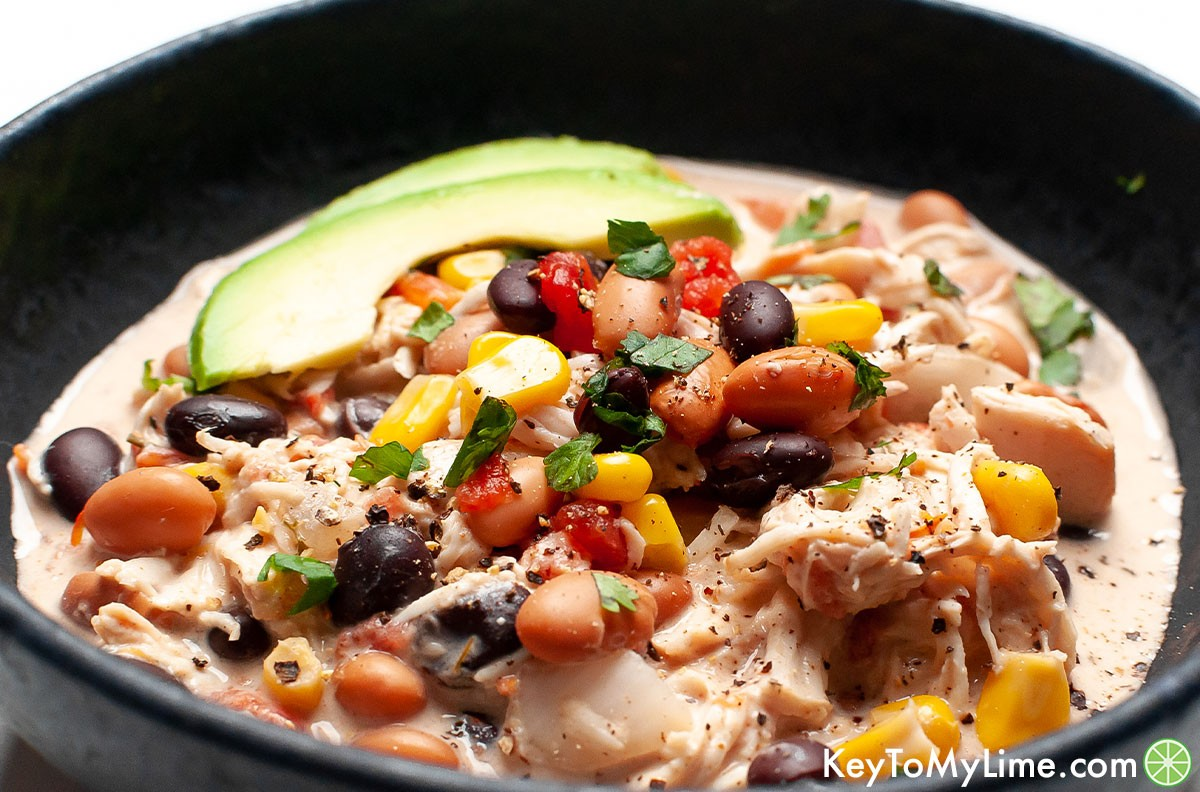 A side image of a bowl of cream cheese chicken chili.