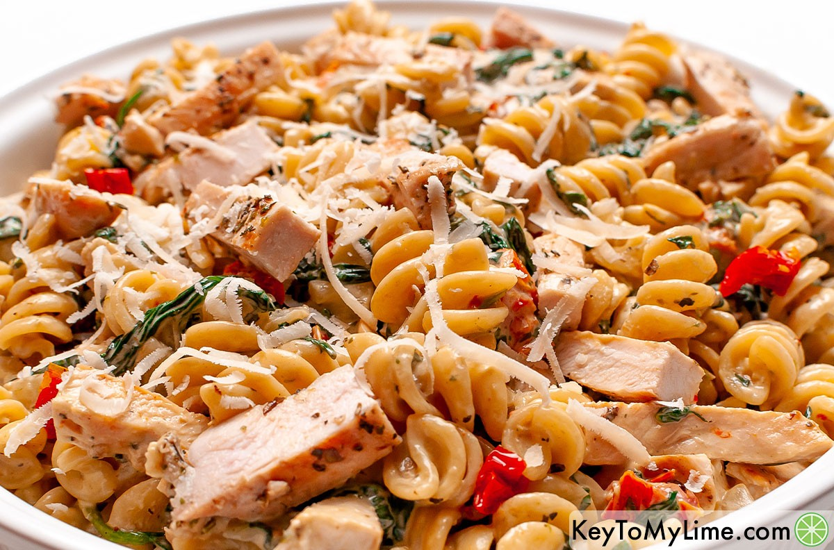 A large white bowl filled with creamy Tuscan chicken pasta.