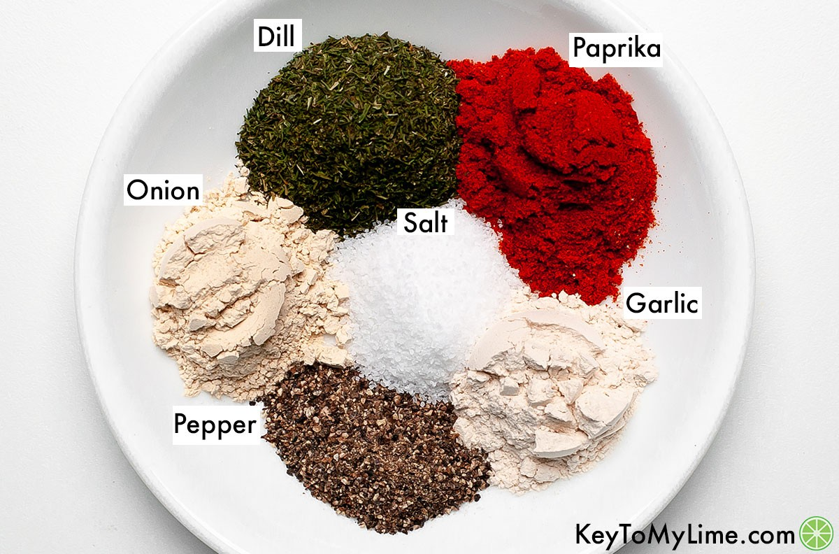 Dill, paprika, garlic powder, onion powder, salt, and pepper in labeled piles on a plate.