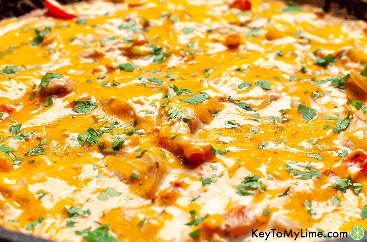 A close up image of fiesta chicken with melted cheese on top.