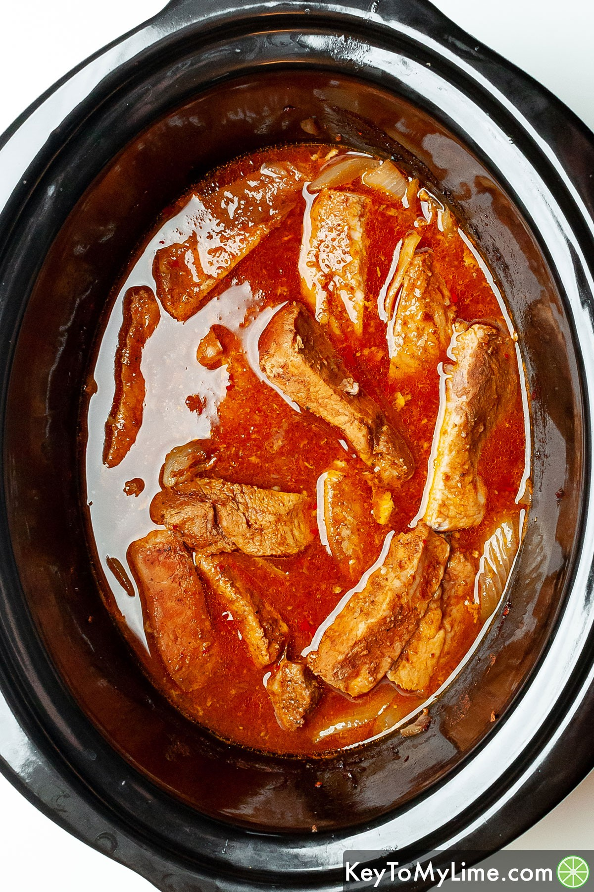 An overhead image of country style pork ribs in the slow cooker.