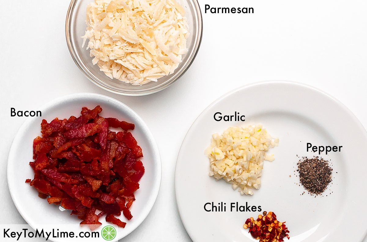 Parmesan, bacon, garlic, chili flakes, and pepper in labeled mounds.