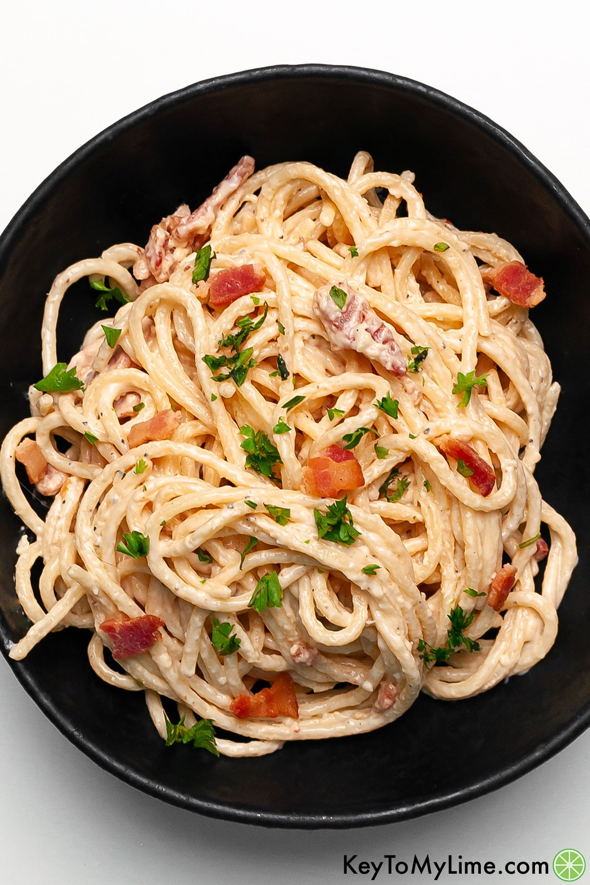 An overhead image of a bowl of cream cheese pasta with bacon and parsley.