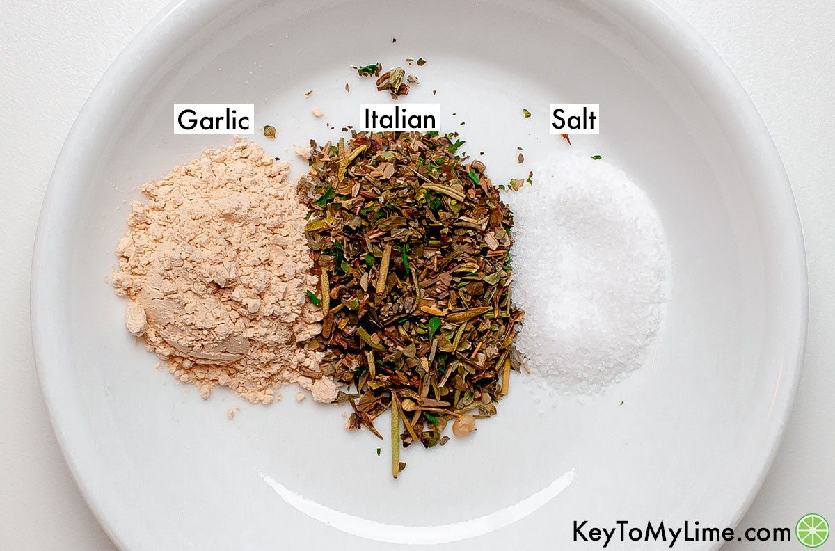 Labeled piles of garlic, Italian seasoning, and salt on a plate.