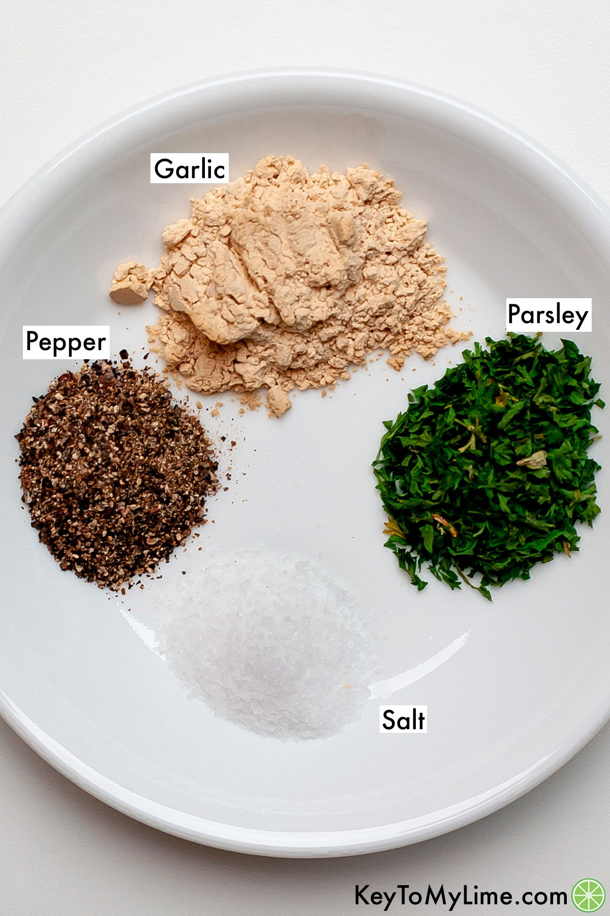 Piles of labeled garlic powder, parsley flakes, black pepper, and salt on a plate.