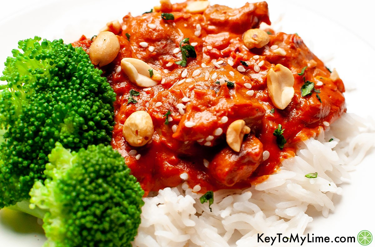 A side image of peanut butter chicken on a white plate.