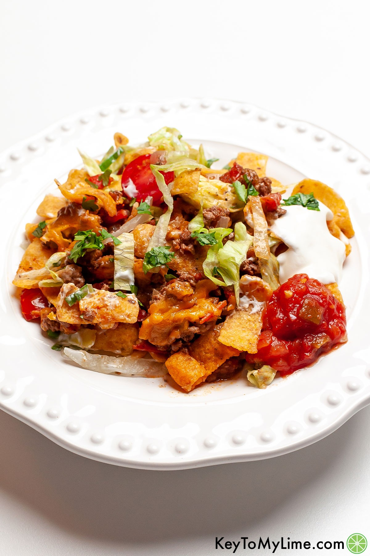 A serving of walking taco casserole on a white plate.