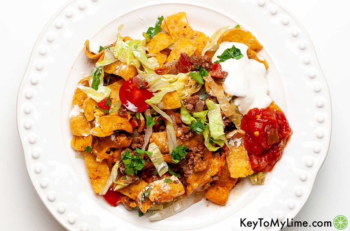 A serving of walking taco casserole on a plate with dollops of salsa and sour cream.